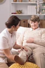 Carer massaging painful leg