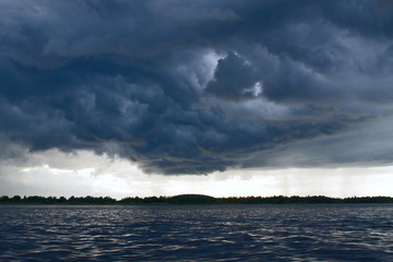 Storm clouds gathering over the forest, view from the sea (the White Sea, the village Kolezhma)