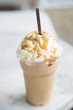 caramel frappe with whipped cream  in the takeaway plastic cup