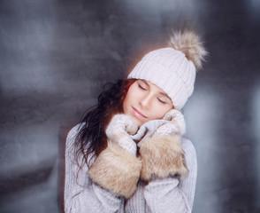Brunette woman in warm winter hat and fur gloves.