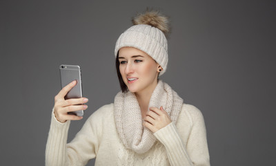 A woman in winter clothes looking at smartphone.