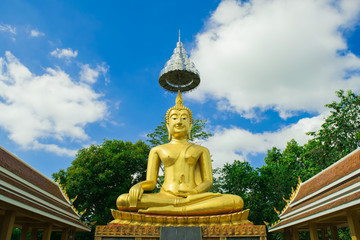 Golden buddha statue with blue sky, Thailand.