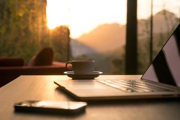 Computer Coffee Mug and Telephone on black wood table sun rising