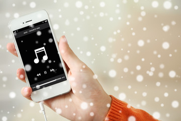 Music smartphone in female hand  over snow effect