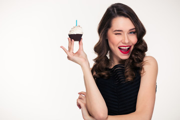 Retro styled woman holding birthday cupcake with candle and winking