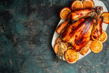 Roast whole turkey or chicken in plate with roasted oranges on dark rustic background, top view