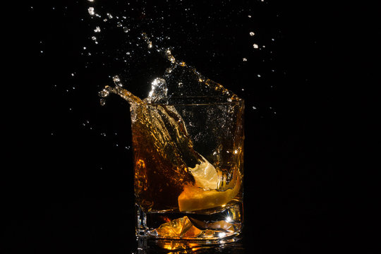 Falling slice of lemon in a quality glass of whiskey makes very many splashes on black background.