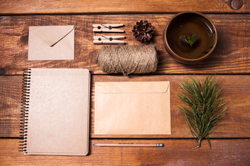 Notebook for recipes, paper envelopess, rope and clothespins on wooden table