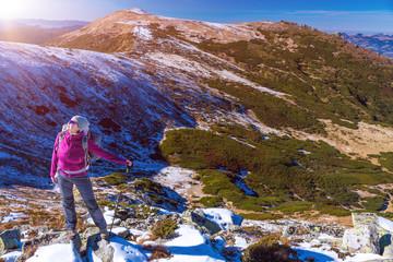 Female Hiker standing on snowy Rocks admiring scenic Winter Mountain View Sun