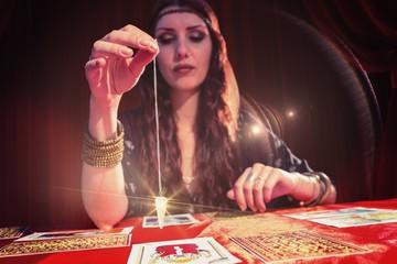Composite image of female fortune teller holding pendulum