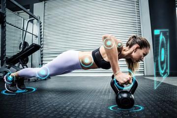 Muscular woman doing pushups with kettlebells