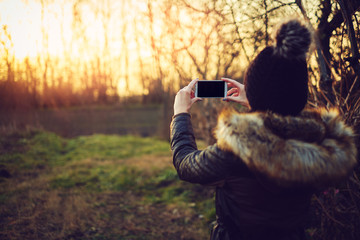Young attractive woman taking photos with smartphone