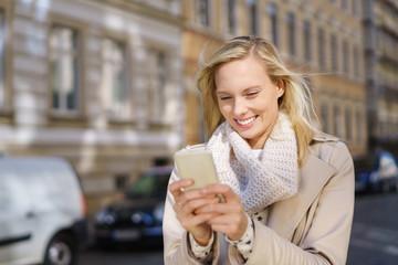 frau steht in der stadt und schaut auf ihr smartphone