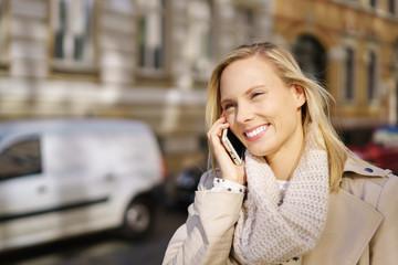 glückliche junge frau geht durch die stadt und telefoniert