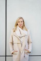 schöne blonde frau steht draußen mit schal und mantel