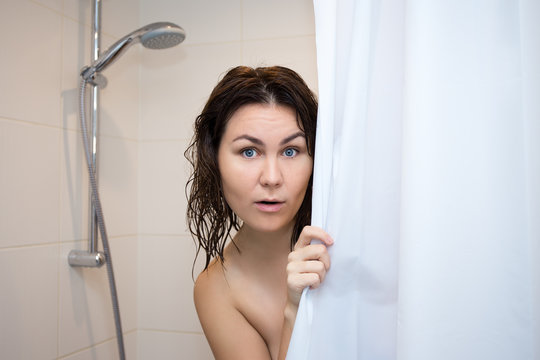 young scared woman hiding behind shower curtain