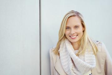 sympathische blonde frau lehnt draußen an einer wand