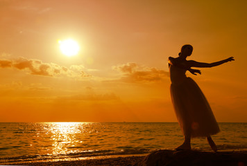 dancing ballerina  at sunset on the coast