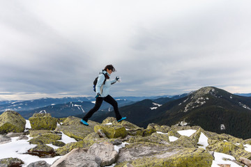 Girl runs along the rocks on the mountain top. Nature