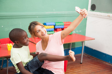 Kid taking a photo with his teacher