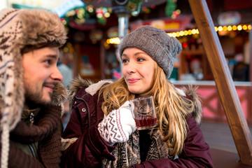Paar Frau Mann hat Spaß auf dem Weihnachtsmarkt sieht sich verliebt an und lacht