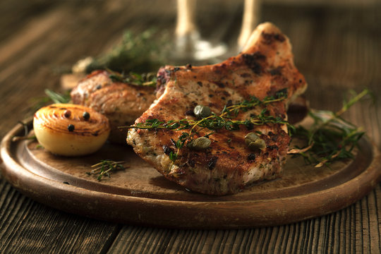 Grilled pork chop with spices, garlic and onions.