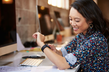 Businesswoman Looking At Smart Watch In Design Office