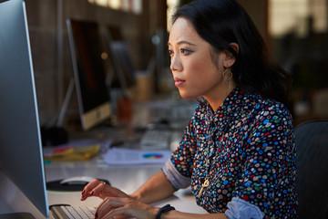 Female Designer Working At Desk In Modern Office