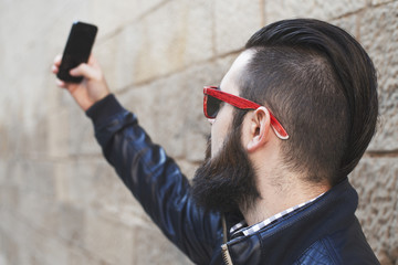 Handsome young man with a beard makes selfie