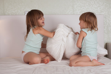 funny girl siblings sisters playing on the bed with pillows
