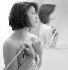 Woman Removing Bra Beside Mirror
