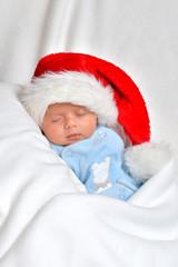 Kleines Baby ist am schlafen und trägt eine Weihnachtsmütze