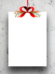Single empty rectangular paper sheet frame with Xmas ribbon decoration on grey concrete wall background