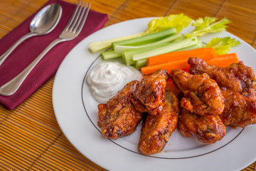 Tasty plate of glazed chicken wings with carrots, celery and dipping sauce.