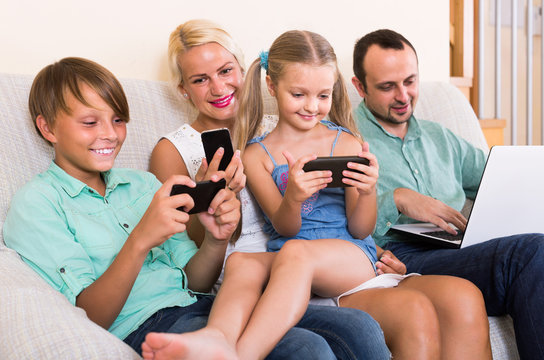 Portrait of  family playing with gadgets at home