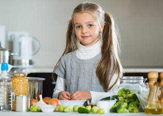 Smiling little girl learning to cook in kitchen