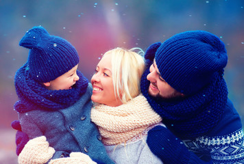 happy family having fun together under winter snow