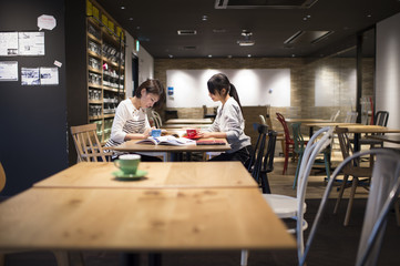 Two women are studying in a cafe