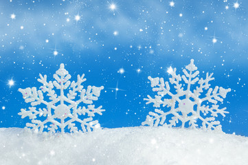 Christmas background with two decorative snowflakes in snow