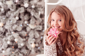 Smiling teenage girl biting gingerbread in bed over Christmas tree. Christmas celebration. Looking at camera. Childhood.