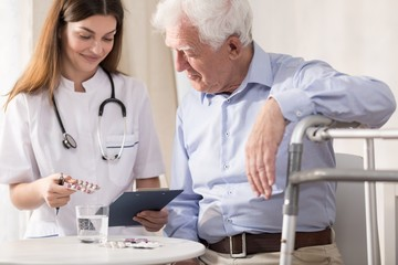 Nurse giving her patient medicines