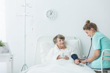 Carer measuring blood pressure
