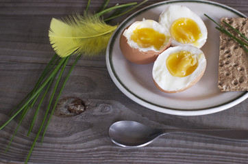 Fresh boiled eggs and green spring onion on plate on wooden tabl
