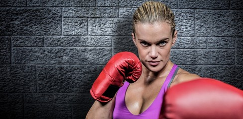 Composite image of portrait of female boxer with fighting stance
