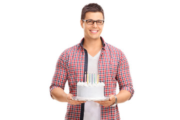 Cheerful young guy holding a birthday cake