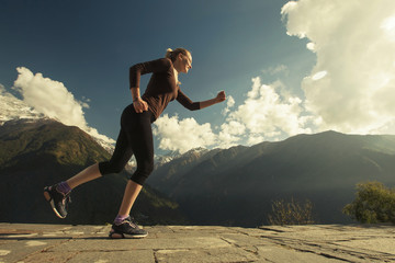 Young Woman Runner in beautiful mountain landscape. Sport exercise outdoor, health care