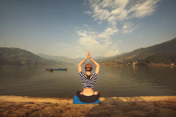 Young female practicing yoga on the shore of mountain lake in morning sunrise