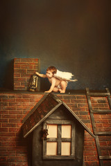 Christmas angel with lamp on the roof . Angel baby with wings. Christmas night, Love Concept
