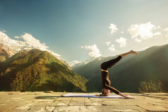 Young woman doing high level yoga asana exercise in mountains outdoor. Morning Fitness, headstand, Sport outdoors, Yoga tours
