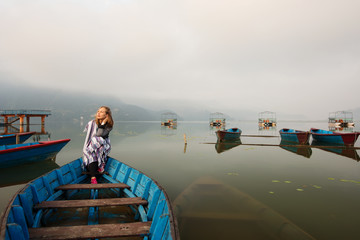Happy meditate girl with blanket sitting in old boat on mountain lake early morning. Clouds and fog over the lake, loneliness, tranquility, relaxation